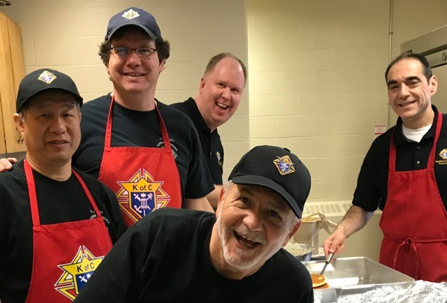 Bros. Sam, Peter, Martin, Michael, and Joe are all smiles working in the kitchen.