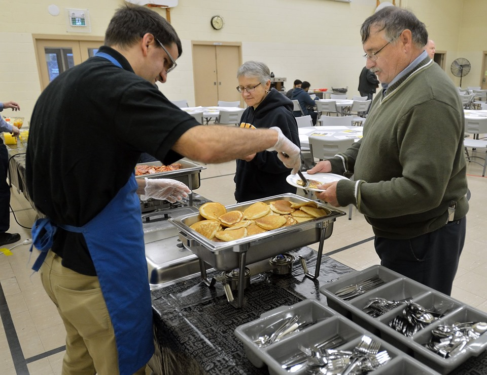 Bro. Nathan Marchand serves Bro. Frank Udovic some pancakes.
