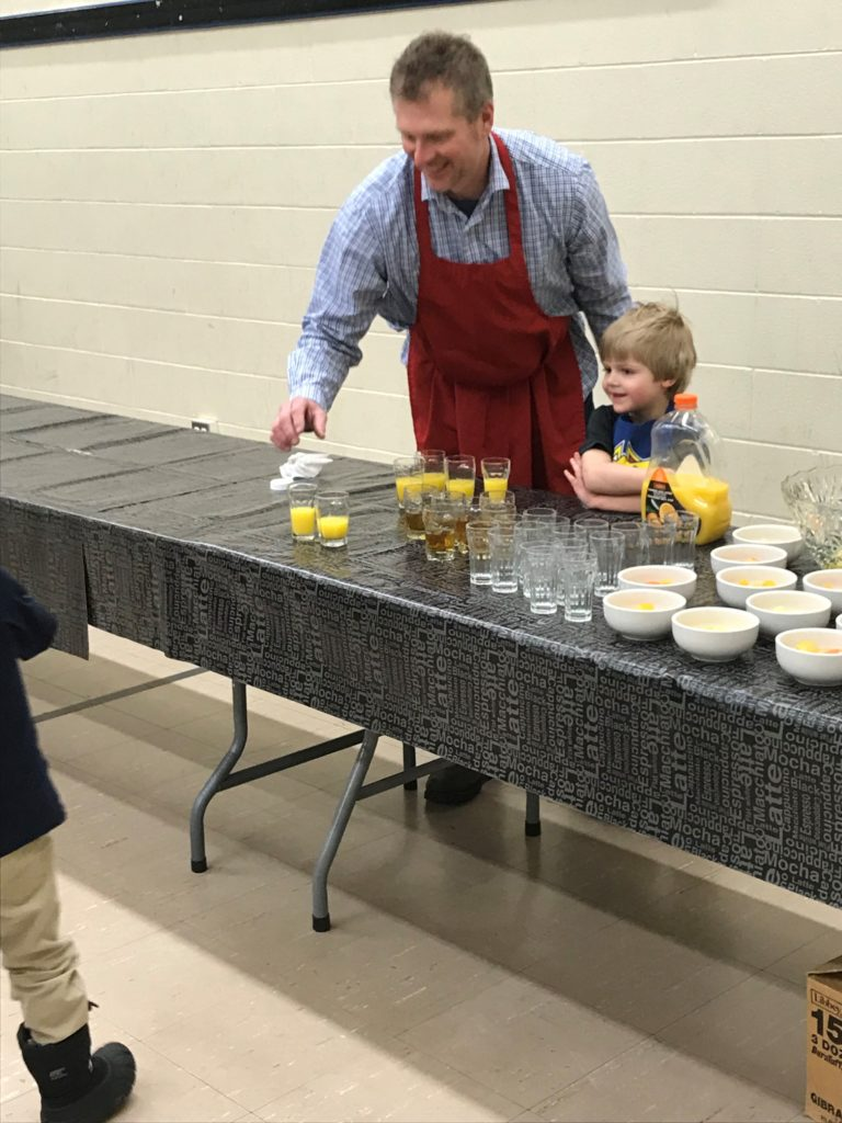 A young parishioner helping his Dad at the breakfast.... a future knight?